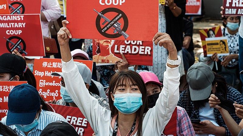 Mulher com máscara de proteção e segurando cartaz em protesto contra o golpe de Mianmar