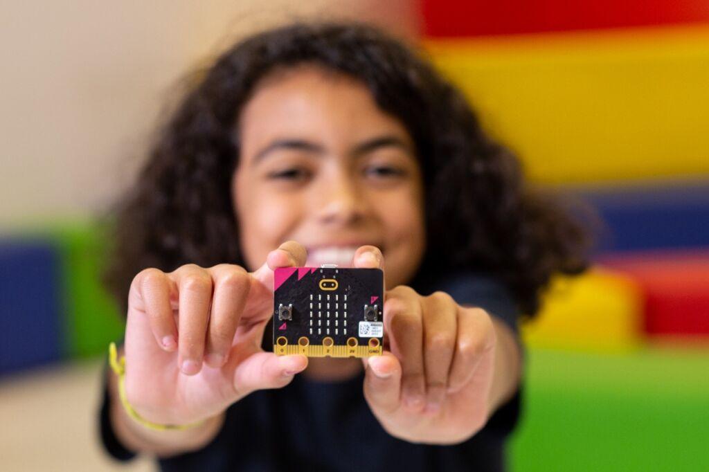 Menina sorrindo mostra placa eletrônica