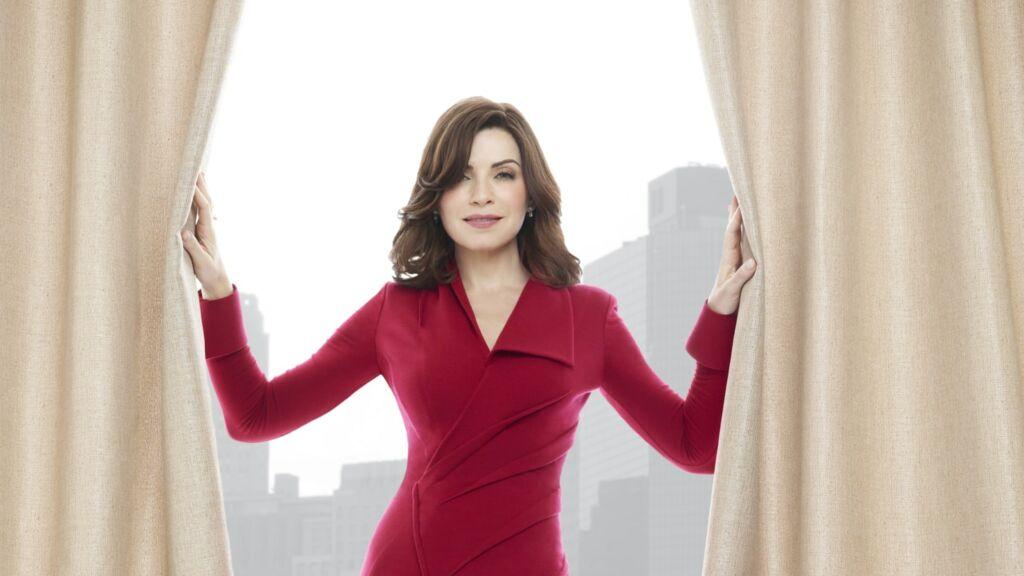 Mulher de frente, vestida de vermelho, segura as cortinas abertas frente a uma grande janela