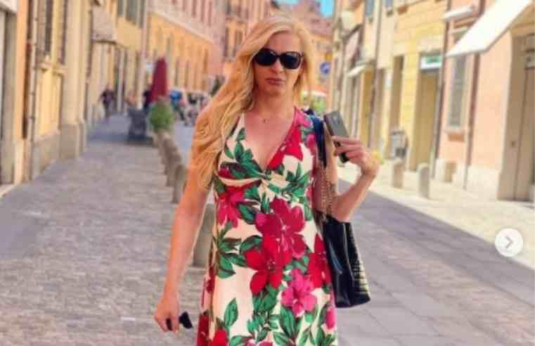 Mel Campos com vestido florido faz pose na rua de uma cidade antiga