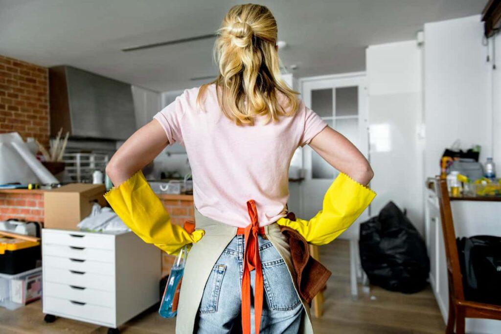 Empregada doméstica, mulher branca loira, de costas com luvas olhando para um cômodo todo bagunçado